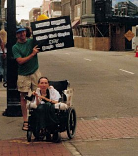 Activist Harriet McBryde Johnson sits in her wheelchair outside with a man behind her holding a protest sign.